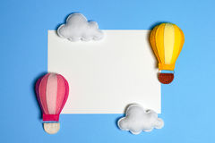 Hot air balloon in blue sky with clouds, frame, copyspace. Hand made felt toys. Abstract sky. Concept for travel agency, motivation, business development royalty free stock photo