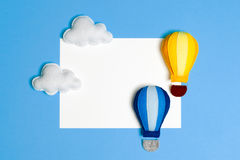 Hot air balloon in blue sky with clouds, frame, copyspace. Hand made felt toys. Royalty Free Stock Photos