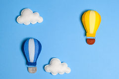 Hot air balloon in blue sky with clouds, frame, copyspace. Hand made felt toys. Abstract sky. Concept for travel agency, motivation, business development royalty free stock image