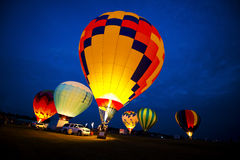 Hot Air Balloon Colors, Evening Night Glow Lights. A group of hot air balloons are lit up as they fire up in an evening glow light show. Each balloon shines with stock image