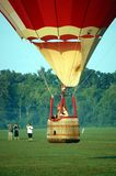 Hot Air Balloon Competition. Hot air balloon descending to a target in the middle of a field at the Hot Air Balloon Championships Royalty Free Stock Image