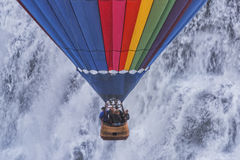 Hot Air Balloon Decending In Front Of A Waterfall Stock Image