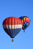 Hot Air Balloon Duet #2. Two colorful hot air balloons soar in a beautiful blue sky Stock Images
