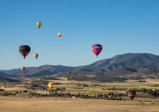 Hot Air Balloon Festival. Colorful hot air balloon's fly through a mountain valley at the Montague Balloon Fair in northern California Stock Photography