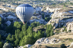 A hot air balloon flies down Love Valley at sunrise near Goreme in the Cappadocia region of Turkey. Royalty Free Stock Image