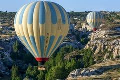 A hot air balloon flies down Love Valley at sunrise near Goreme in the Cappadocia region of Turkey. Royalty Free Stock Photo