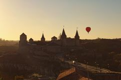 Hot air balloon flies near Kamianets-Podilskyi castle. It is famous touristic place and romantic travel destination. Beautiful autumn sunset landscape royalty free stock photography