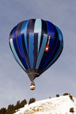 Hot Air Balloon Flies over a peak Royalty Free Stock Images