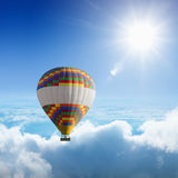 Hot air balloon flies very high in blue sky Royalty Free Stock Image