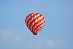 Hot Air Balloon in Flight. Red and white striped hot-air balloon in flight Stock Image
