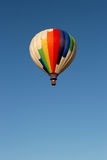 Hot air balloon in flight. White balloon with rainbow colors against clear blue sky stock photo