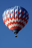 Hot air balloon in flight. Red, white and blue hot air balloon in flight with sky background and copy space Royalty Free Stock Photo