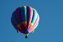 Hot air balloon in flight. Colorful hot air balloon in flight with blue sky background and copy space Royalty Free Stock Images