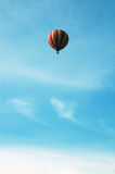 Hot air balloon in flight. Red and yellow hot air balloon in flight in a blue sky Stock Photo