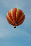 Hot air balloon in flight. Low angle view of colorful hot air in flight with blue sky background stock images