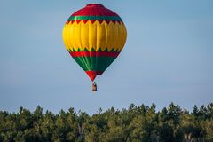 Hot air balloon in flight against a background of blue sky. A moment of flight over a vast green deciduous forest.