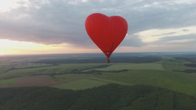 Hot air balloon flight. Heart shaped balloon at sunset