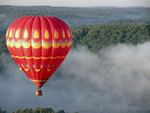 Hot Air Balloon Flight. Red and yellow Hot-Air Balloon soaring above trees and fog Stock Photos