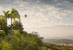 Hot Air Balloon In Flight, San Diego, California. A colorful hot air balloon after lift off in Del Mar, California, viewed from a hillside in the northern San royalty free stock image
