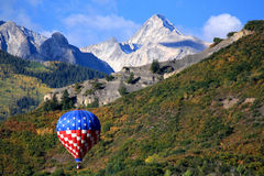 Hot air balloon floating through mountains Stock Photography
