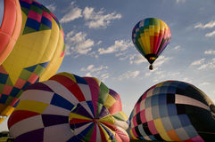Hot air balloon floating over other inflating balloons Stock Images