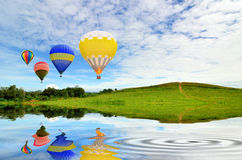 Hot air balloon floating. In the sky over green grass Royalty Free Stock Photo