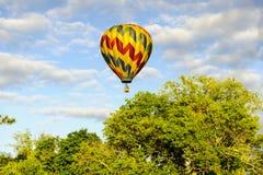 Hot air balloon floats away. Quechee, Vermont, USA - June 19, 2009: Hot air balloon floats off into the distance at the Quechee Hot Air Balloon Craft and Music Stock Image
