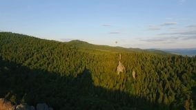 Hot Air Balloon fly through the sky in a landscape of mountains near the rocks stock video footage