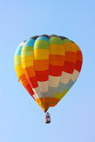 Hot air balloon flying. A coloured hot air balloon flying in the sky Stock Images