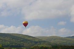 Hot Air Balloon Flying Above the Mountains on a Hazy Morning Stock Photos