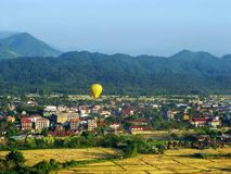 Hot air balloon flying above Vang Vieng town, Vientiane Province stock photography