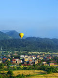 Hot air balloon flying above Vang Vieng town, Vientiane Province. Laos. Vang Vieng is a popular destination for adventure tourism in a limestone karst Royalty Free Stock Image