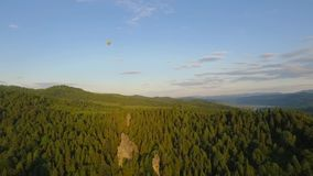 Hot Air Balloon flying across the sky in mountains landscape stock video