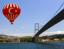 Hot air balloon flying Bosphorus bridge Stock Photography