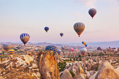Hot air balloon flying over Cappadocia Turkey. Hot air balloon flying over rock landscape at Cappadocia Turkey Royalty Free Stock Image