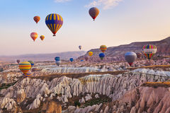 Hot air balloon flying over Cappadocia Turkey. Hot air balloon flying over rock landscape at Cappadocia Turkey stock photos