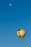 Hot Air Balloon flying over clear blue sky with Moon Stock Photo