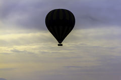 Hot Air balloon flying over the clouds. Silhouette of a hot air balloon high in the sky Royalty Free Stock Photos