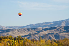 Hot Air Balloon Flying Over The Foothills Stock Photo