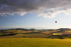 Hot air balloon flying over a golf course. And amazing valley at sunset Royalty Free Stock Photo