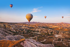 Hot air balloon flying over Cappadocia Turkey. Hot air balloon flying over rock landscape at Cappadocia Turkey Royalty Free Stock Images