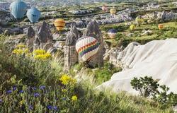 Hot air balloon flying over rock landscape at Cappadocia Stock Photography