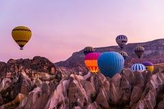 Hot air balloon flying over spectacular Cappadocia, Tourists enjoy the overwhelming views over Cappadocia, Turkey royalty free stock image
