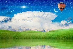 Hot air balloon flying in starry sky to new moon. Idyllic peaceful background - hot air balloon rise up into blue starry sky above green meadow to new moon Stock Image