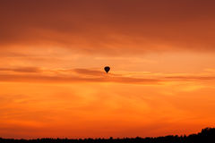 Hot air balloon flying at sunset sky Royalty Free Stock Image