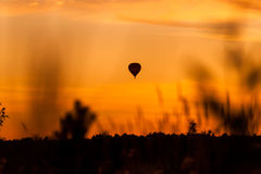 Hot air balloon flying at sunset sky Stock Image