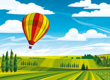 Hot air balloon and green rural meadow Royalty Free Stock Photo