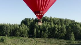 Hot air balloon in heart shape flying over green field. Red love air balloon stock video