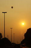 Hot air balloon higher then sun!. Silhouette of hot air balloon over highway while sun sets Stock Photo