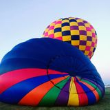 Hot air balloon inflation two square bright colors. Orange green yellow red blue stripes inflation for launch of hot air balloons Royalty Free Stock Photos
